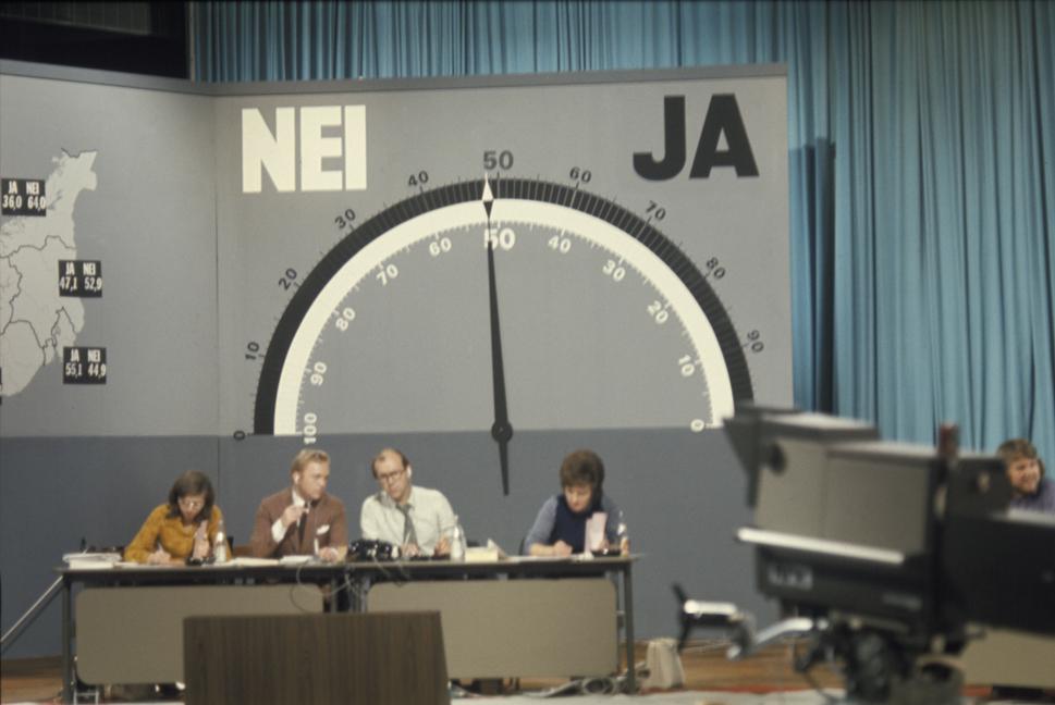 Folkeavstemningen om Medlemskap i det Europeiske Fellesskap, EF : Folkeavstemning om EF. Her fra valgvaken i NRK studio med barometeret som viser hvoran Ja og Nei siden stŒr. Pilen tipper mot flertall for Nei. De endelige tallene ble 53.49 prosent for Nei og 46.51 prosent for Ja. Programlederne i midten er Lars Jacob Krogh (th) og Geir Helljesen.<br />